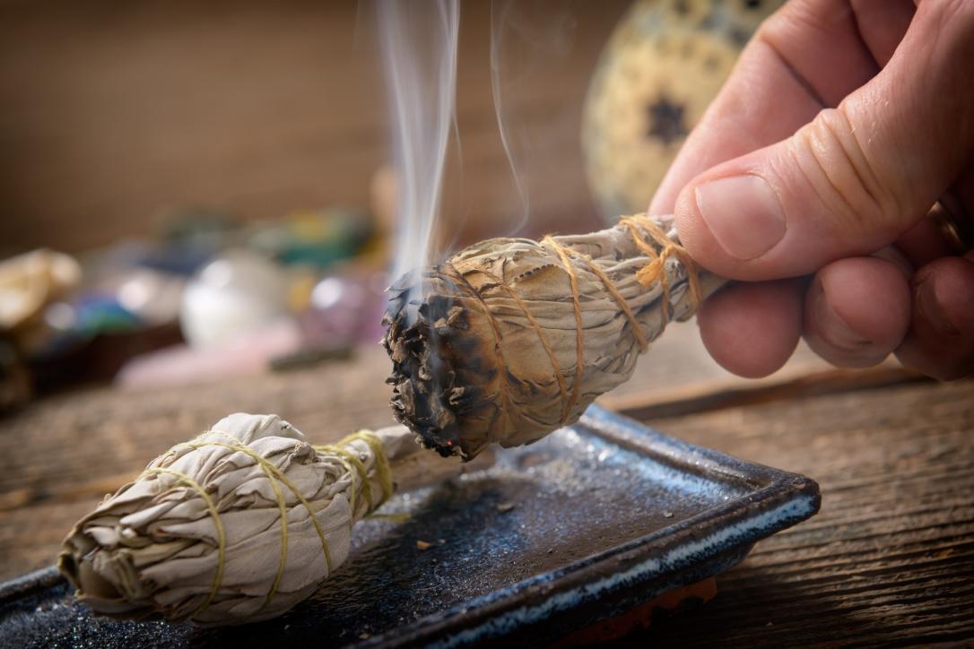 Man burning white sage incense