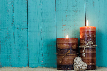 Candles by rope heart and rustic wood background